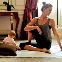 Modelo Gisele Bündchen pratica yoga enquanto sua filha brinca